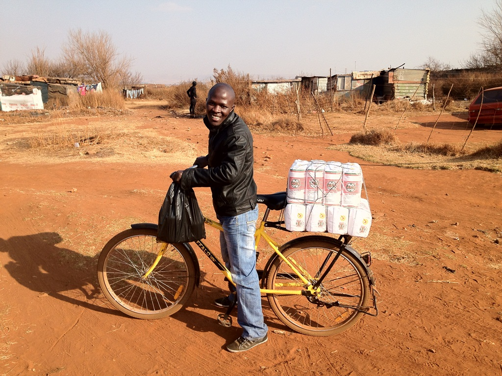 As you can see in the photo, this man uses his Qhubeka bicycle to buy flour in bulk and then sell it in his community