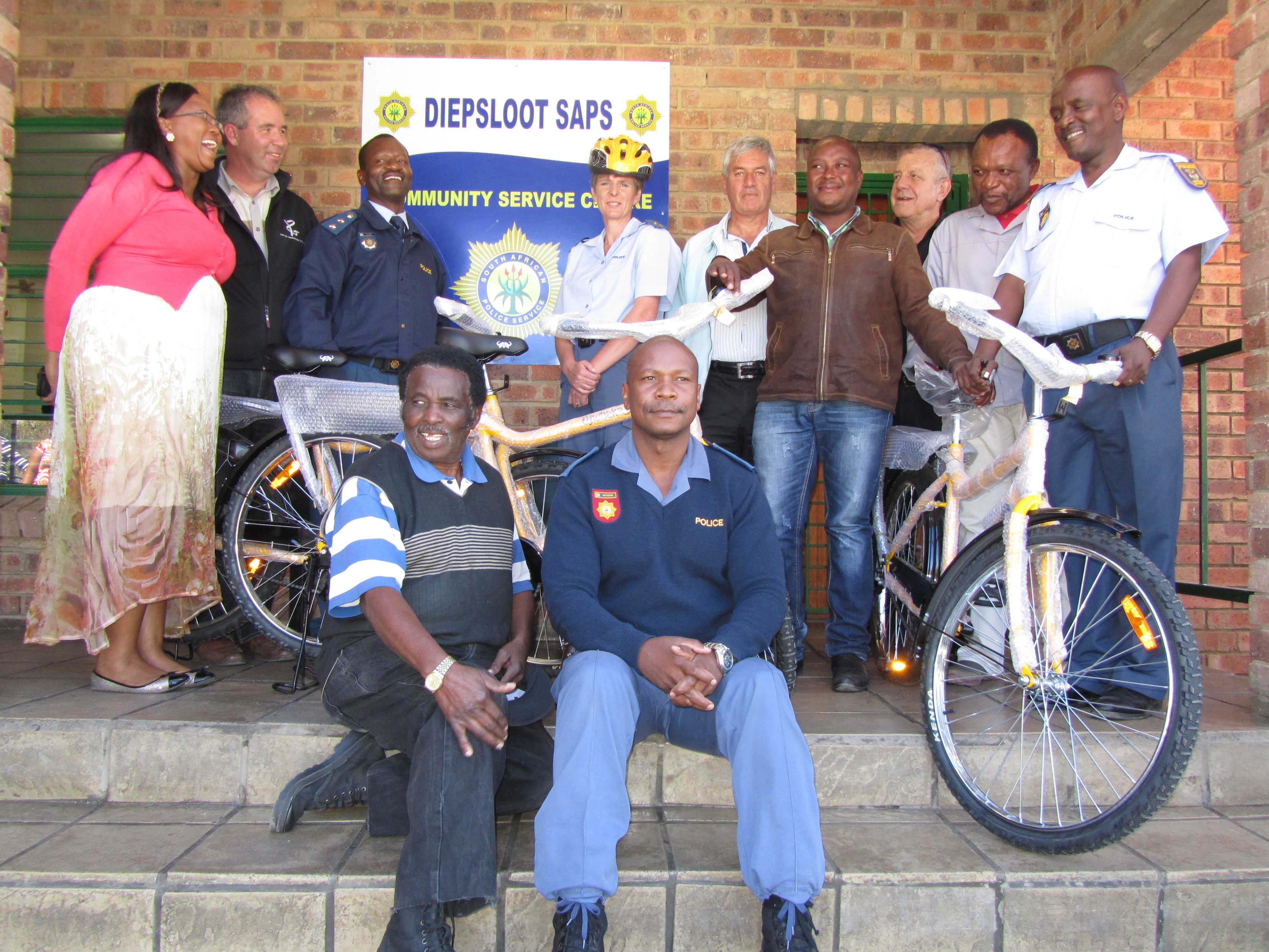 Attending the handover of the bicycles were (back from left) Lt.Col. Mkhaliphi, Pastor Willem Lindeque, Col. Balatse, Lt.Col. Serfontein, Reg Bernstein General Manager of the DHA, Peter Motatjane of the Diepsloot CPF, Giovanni Mottalini of Qhubeka Bicycles, James Mkansi and Warrant Officer Segoe. (seated front) Deputy Chairperson of the Diepsloot CPF Mr N.Legodi and Capt. Matabane.