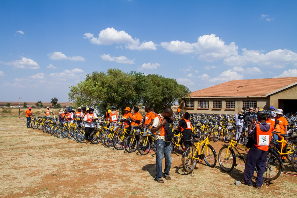 World Vision volunteers stand ready to hand over the bicycles to their excited new owners.