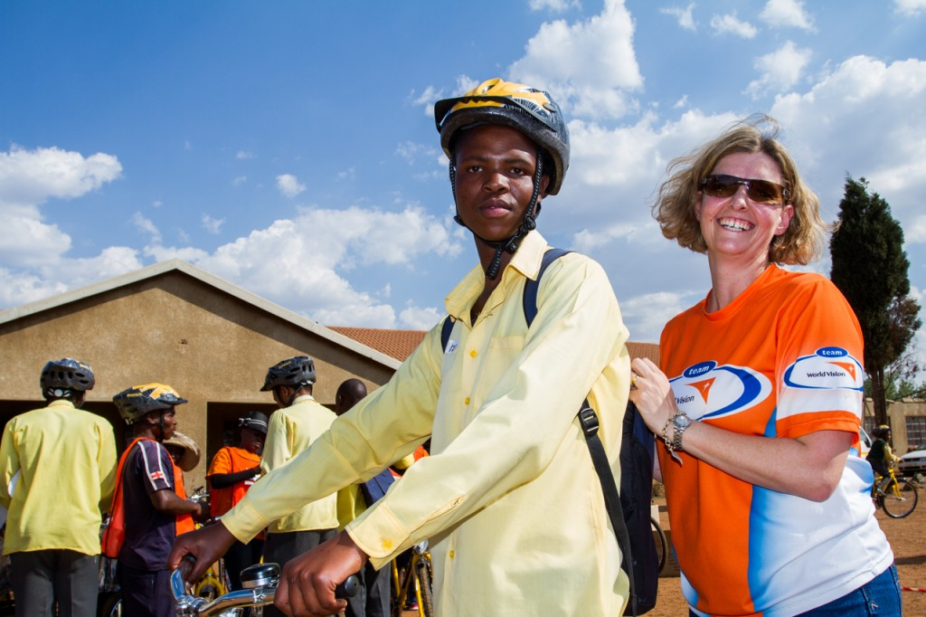 Paula Barnard (National Director, World Vision SA), ensures helmets are securely fitted before letting recipients ride home.