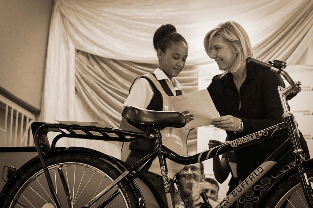 Albi Breen, Sales Executive for Dimension Data MEA, welcomes bicycle recipients to the stage one by one.