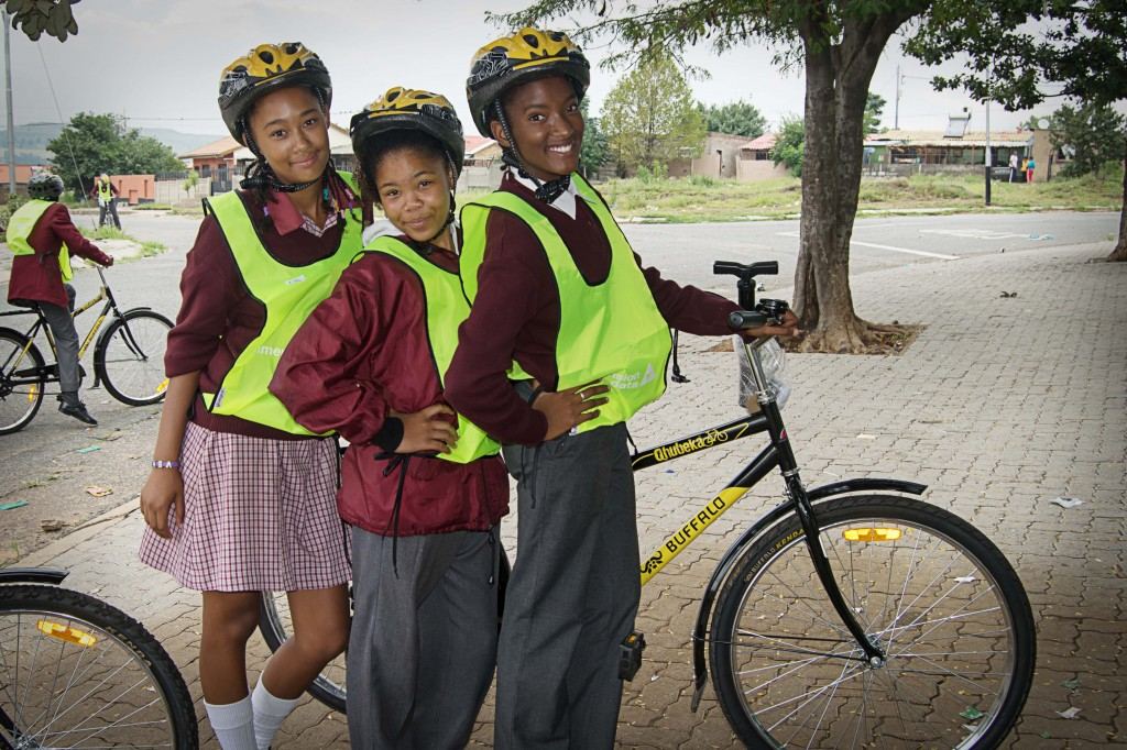 Three young women pose with one of the new bicycles.