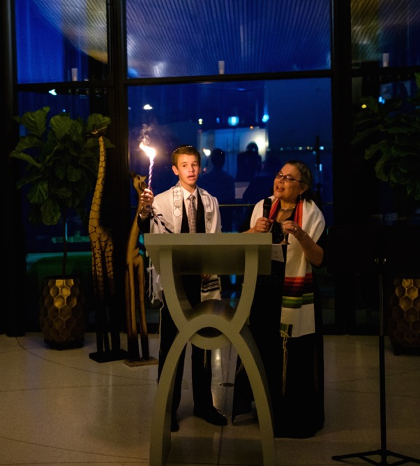 """A photo from during Jacob's Bar Mitzvah ceremony. """"My Torah portion was about Noah's ark. That is why there are two wooden giraffes behind us and the ceiling in the room was the keel of a boat (reflected in the window). The picture shows me holding the Havdallah candle and Jo Anne Chisholm, the leader who ran the service, chanting."""""""